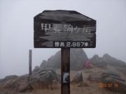 甲斐駒ヶ岳山頂と岩陰で身を守る登山者