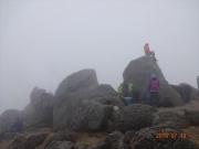 山頂で雲が晴れるのを待つ登山者達