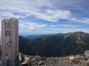 聖岳山頂にて、背景に赤石岳
