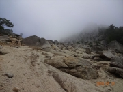 霧に包まれた山頂への砂礫登坂道
