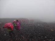 霧雨の中のツアー登山者の列