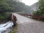 増水した川に架かる橋を渡る