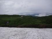 雪渓上から見下ろす祓川神社鳥居とヒュッテ
