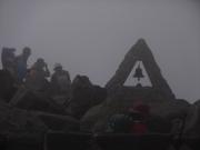 濃霧の山頂に赤子背負いの登山者